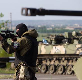 Image: A Ukrainian soldier points his weapon at an approaching car with armoured personnel carriers behind him at a checkpoint near the town of Slaviansk in eastern Ukraine