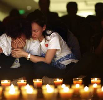 Image: A family member cries as she and other relatives pray during a candlelight vigil
