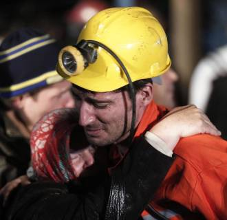 Image: A miner hugs a relative in front of a coal mine site in Soma, Manisa