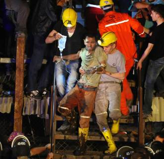 Image: An injured miner is carried to an ambulance after being rescued from a coal mine he was trapped in Soma