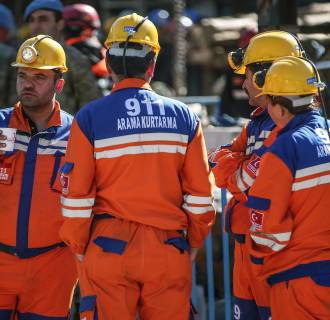 Image: Turkish rescue workers stand at the entrance of the coal mine in Soma, Turkey, Friday, May 16, 2014.
