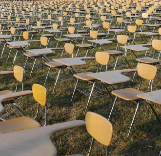 Image: An art installation of 857 empty school desks stands at the National Mall in Washington