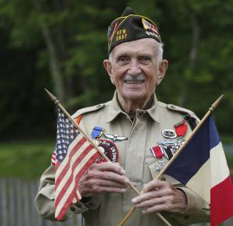 Image: US World War II veteran Jack W. Schlegel poses with American and French flags as he visits the American War cemetery in Colleville-sur-Mer