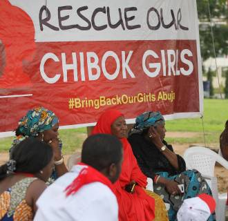 Image: A member of the #BringBackOurGirls Abuja campaign group addresses a protest in Abuja