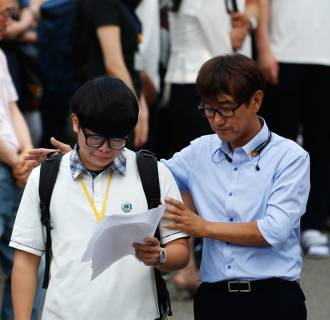 Image: A student who survived the April 16 ferry disaster cries while reading a letter as a teacher comforts him at Danwon Highschool in Ansan