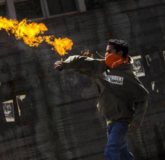 Image: A protester throws a molotov cocktail at Bolivarian National Police
