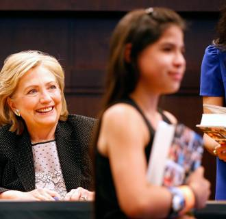 Image: Hillary Clinton smiles during a book signing for her book
