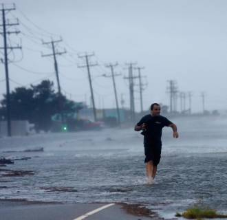 Image: A man crosses a flooded Highway 64