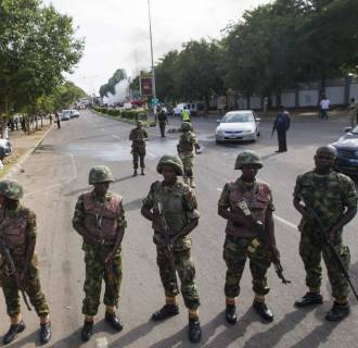Image: Soldiers cordon off a road leading to the scene of a blast at a business district in Abuja