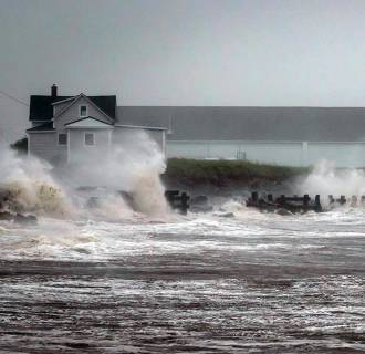 Image: Waves crash against rock embankments that protect the Escuminac road against erosion during Tropical storm Arthur in Escuminac, New Brunswick