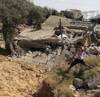 Image: Palestinians inspect the rubble of a house after it was hit by an Israeli missile