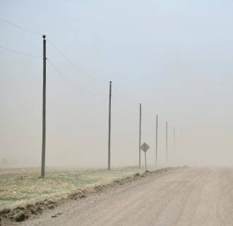 Image: The relentless Kansas wind strips a dry, bare field and sends the topsoil to obscure a county road