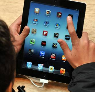 Image: A young person looks at an iPad