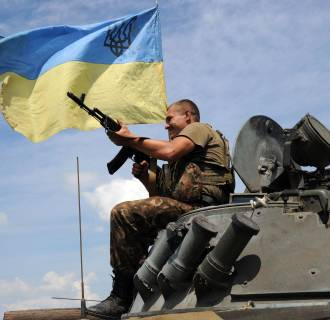 Image: A Ukrainian government soldier sits atop an armored vehicle