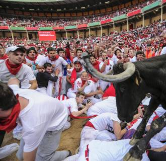 Image: A cow jumps over revelers on the bull ring at the San Fermin festival