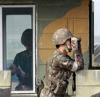 Image: A South Korean army soldier looks through a pair of binoculars at a military check point