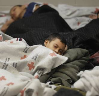 Image: Detainees sleep in a holding cell at a U.S. Customs and Border Protection processing facility, June 18, 2014, in Brownsville, Texas.
