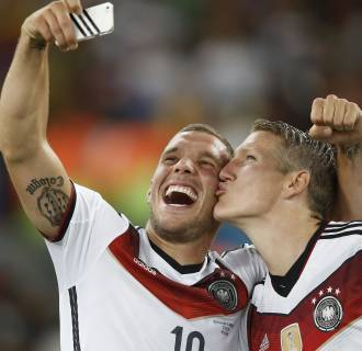 Image: Germany's midfielder Bastian Schweinsteiger and Germany's forward Lukas Podolski take a 'selfie' after their victory