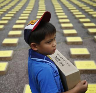 Image: A boy holds a box containing signatures of South Koreans petitioning for the enactment of a special law after the Sewol ferry disaster