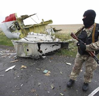 Image: A pro-Russian separatist stands at the crash site of Malaysia Airlines flight MH17, near the settlement of Grabovo in the Donetsk region