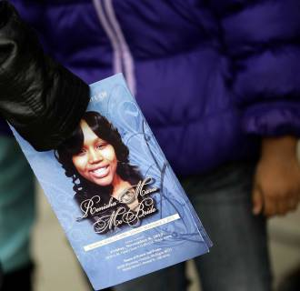 Image: A mourner holds an obituary displaying a picture of shooting victim Renisha McBride during her funeral service in Detroit