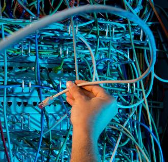 Image: A photographic illustration shows a hand working on cables inside a server room