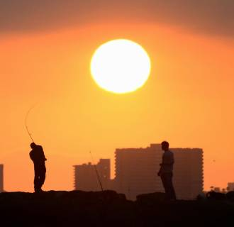 Image: A fisherman casts his line from the rocks at Seal Beach, California