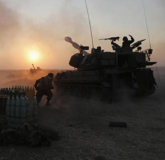 Image: An Israeli mobile artillery unit fires towards the Gaza Strip