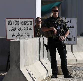 Image: A foreign security contractor from a security company keeps watch at the site of an incident after a blast, outside the counter-narcotics office near the Kabul International Airport