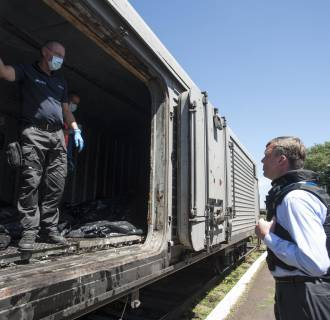 Image: Deputy head of the OSCE mission to Ukraine Alexander Hug, right, speaks to a member of Netherlands' National Forensic Investigations team on the platform as a refrigerated train loaded with bodies of the passengers departs the station in Torez