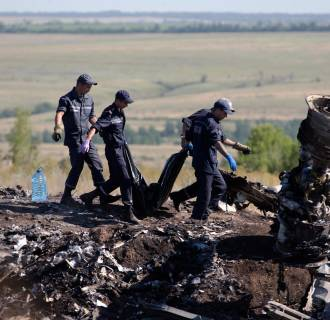Image: Ukrainian emergency workers carry a victim's body in a plastic bag at the crash site of Malaysia Airlines Flight 17
