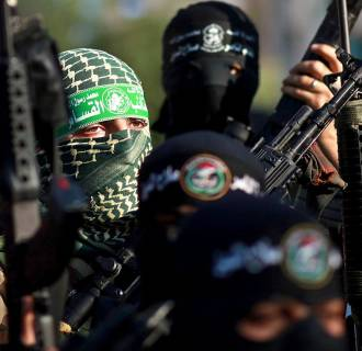 Image: Palestinian militants, including Ezz Al-Din Al Qassam militia, the military wing of the Hamas movement, gather next to the Palestinian parliament