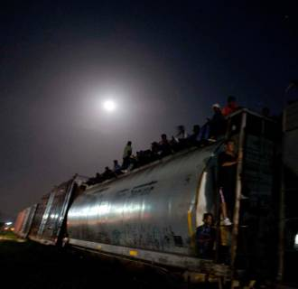 Image: Central American migrants wait on a stopped freight train during their journey toward the U.S.-Mexico border after reports that robbers had boarded the train and where stealing from the migrants, in Chahuites, Mexico
