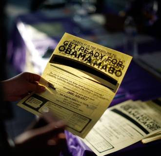 Image: A woman picks up a leaflet at a health insurance enrollment event in Cudahy, Calif.