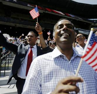 Image: Newly-sworn in U.S. citizens cheer during a naturalization ceremony for more than 1,000 citizenship candidates at Turner Field, home of the Atlanta Braves baseball team, on July 2, in Atlanta.