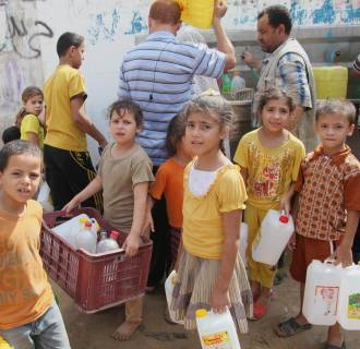 Image: Palestinian kids fill water bottles in Khan Younis on Monday