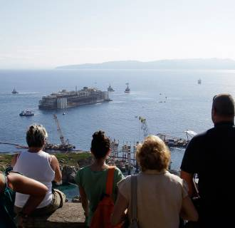 Image: People look out as the Costa Concordia wreck is towed away