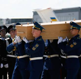 Image: Honor guards carry the coffin of a Malaysia Airlines MH17 victim at Kharkiv airport