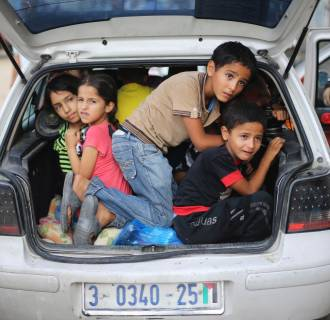 Image: Palestinian children sit in a car boot as they flee their family homes following heavy Israeli shelling during an Israeli ground offensive east of Khan Younis, in the southern Gaza Strip