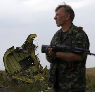 Image: A pro-Russian separatist stands guard as monitors from Organization for Security and Cooperation in Europe and members of a Malaysian air crash investigation team inspect the crash site of Malaysia Airlines Flight MH17 near the village of Hr