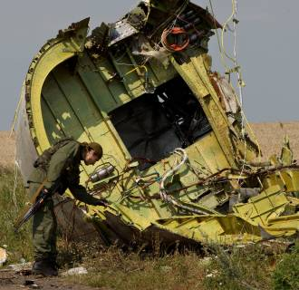 Image: A pro-Russian rebel touches the MH17 wreckage at the crash site