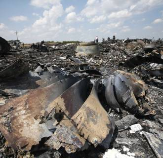 Image: People walk near the wreckage of Malaysia Airlines MH17 that crashed last Thursday, near Hrabove