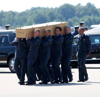 Image: A coffin of one of the victims of Malaysia Airlines MH17 downed over rebel-held territory in eastern Ukraine, is loaded into a hearse on the tarmac during a national reception ceremony at Eindhoven airport July 23, 2014.