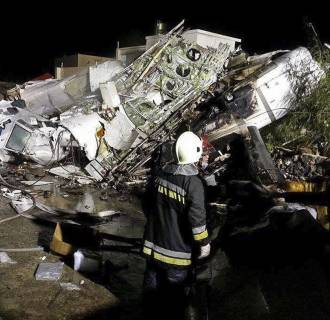 Image: Rescue workers survey the wreckage of TransAsia Airways flight GE222 which crashed while attempting to land in stormy weather on the Taiwanese island of Penghu, late Wednesday, July 23, 2014.