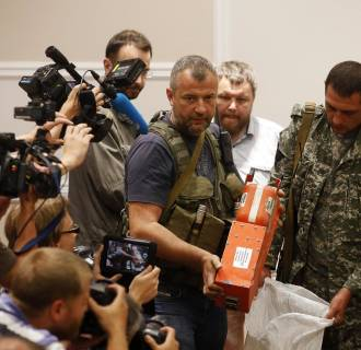 A pro-Russian separatist shows members of the media the