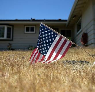 Image: An American flag is displayed on a dead lawn in front of a home in Fremont, Calif.