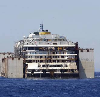 Image: Tugboats drag cruise liner Costa Concordia after leaving Giglio Island