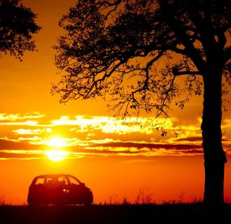 Image: A car drives at sunset.