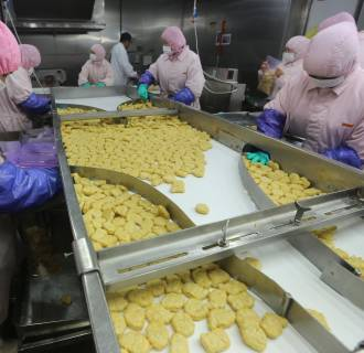 Image: Employees work at a production line prior to a seizure at the Husi Food factory in Shanghai