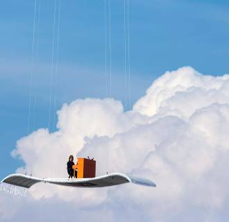 Image: German pianist Stefan Aaron plays an orange piano on a 'flying carpet' platform suspended from a helicopter, over the Munich airport